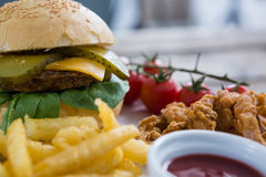Close up of burger and fries with onion rings by sauce. On table Royalty Free Stock Photos