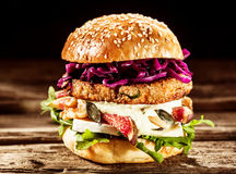 Close Up of Burger Piled High with Fresh Toppings. Close Up of Gourmet Burger Piled with Fresh Toppings on Whole Grain Bun, on Rustic Wooden Surface Royalty Free Stock Images