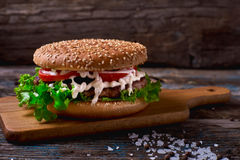 Close Up of Burger Piled High with Fresh Toppings on Whole Grain Artisan Bun, on Rustic Wooden Surface with Dark Background and Co Royalty Free Stock Image