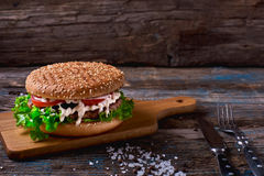 Close Up of Burger Piled High with Fresh Toppings on Whole Grain Artisan Bun, on Rustic Wooden Surface with Dark Background and Co Royalty Free Stock Photo