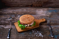 Close Up of Burger Piled High with Fresh Toppings on Whole Grain Artisan Bun, on Rustic Wooden Surface with Dark Background and Co Stock Image