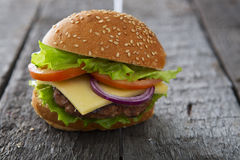 Close Up of Burger on Rustic Wooden Surface Royalty Free Stock Photography