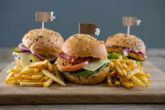 Close up of burgers with french fries served on cutting board Stock Photo