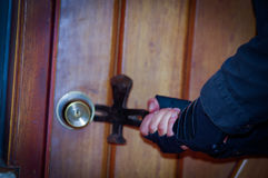 Close up of a burglar with crowbar trying break the door to enter the house.  royalty free stock photography