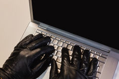 Close up of burglar hacking a laptop Royalty Free Stock Photography
