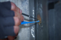 Close up of a burglar holding Lock-picker to open a housedoor.  stock photo