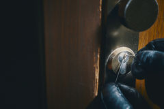 Close up burglar picking a lock. Close up of a burglar with gloves picking a lock royalty free stock image