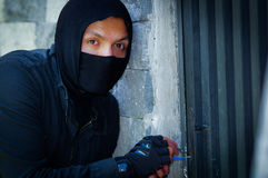 Close up a burglar wearing a mask holding a lock-picker to open a housedoor.  Royalty Free Stock Image