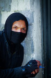 Close up a burglar wearing a mask holding a lock-picker to open a housedoor.  Stock Photography