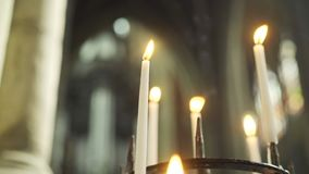Burning candles in church. Close-up burning candles in candelabrum, interior of ancient cathedral at blurred backgroung. Flame flapping on the wind rising smoke stock footage