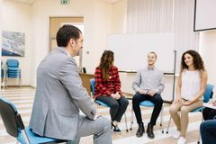 Office staff talking and sitting in a circle on a light room background. Discussion concept. stock image
