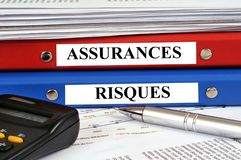 Folders insurance and risk written in french stock photo
