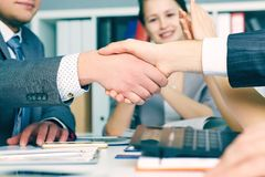 Close up business handshake on team meeting with clapping group of people blured in background at modern startup stock photo