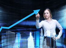Close up of the business lady who points out the growing arrow, which symbolises the concept of the success. Stock Photos