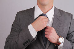Close up of business man adjusting his neck tie. Business and finance concept. Stock Image
