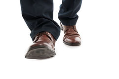 Close-up of business man elegant shoes walking. Isolated on white background Stock Photos