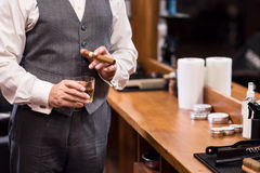 Close up of business man with glass and cigar. Status symbol. Close-up of rich man wearing luxury suit standing with whiskey glass and cigar at barbershop royalty free stock images