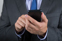 Close up of business man hands holding mobile phone Stock Images
