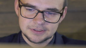 Close up of business man's face smiling and looking on the laptop. Slowly stock video