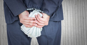 Close up of business man`s hands behind back with money and handcuffs against grey wood panel Royalty Free Stock Image