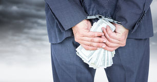 Close up of business man`s hands behind back with money and handcuffs against white wall. Digital composite of Close up of business man`s hands behind back with Stock Images