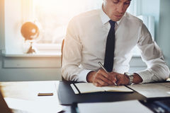 Close up of business man in shirt and tie working. In his office writing in a classic note book Stock Photos