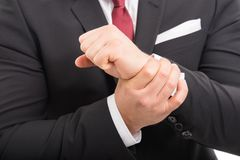 Close-up of business man standing holding wrist like hurting Stock Images