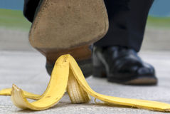 Close up business man stepping on banana skin Royalty Free Stock Photos