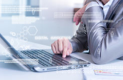 Close up of business man typing on laptop conputer with technology layer effect stock photography