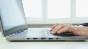 Close up of a business man typing on a silver laptop. stock footage