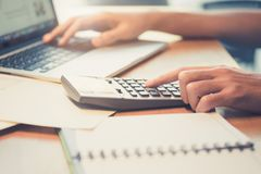 Close up Business man using calculator and laptop computer for c Stock Images