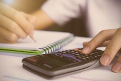 Close up Business man using calculator and writing on notebook f Royalty Free Stock Photo