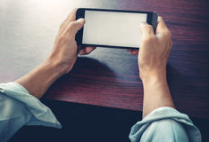Close up of a business man using mobile smart phone at wooden table Royalty Free Stock Photography
