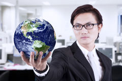 Close-up business manager hold globe at office. Asian businessman looking smart with glasses holding a globe at office Stock Photos