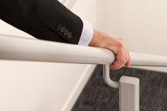 Hold the handrail. Close up of a business mans hand holding a handrail while descending the stairs. Selective focus used stock photo