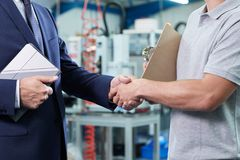 Close Up Of Business Owner With Digital Tablet In Factory Shaking Hands With Engineer stock photography