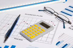 Close up of business papers with graphs, charts, glasses, pen an Stock Image