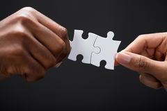 Hands Combining White Puzzle Pieces. Close-up Of Business Partners Combining Two White Puzzle Pieces On Black Background royalty free stock images
