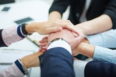 Close-up of business partners making pile of hands. royalty free stock photos