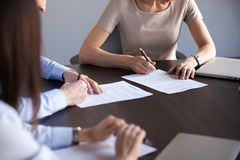 Close up of business partners man and woman signing contract. Close up view of new business partners fill document form sign two-sided contract concept, men and royalty free stock photography