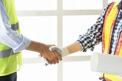 Close-up of business people handshaking .Handsome construction w royalty free stock photography
