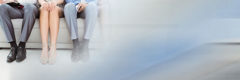 Close up of business people legs on couch with blurry blue and grey transition Stock Image