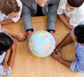 Close-up of business people looking at a globe stock image