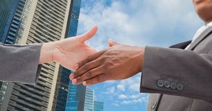 Close-up of business people shaking hands in city. Digital composite of Close-up of business people shaking hands in city Stock Photography