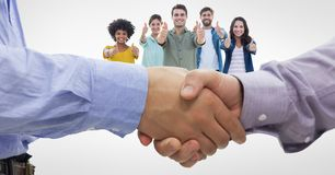 Close-up of business people shaking hands while colleagues gesturing thumbs up. Digital composite of Close-up of business people shaking hands while colleagues Stock Image