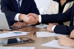 Close up of business people shaking hands at meeting or negotiation in the office. Partners are satisfied because. Signing contract stock photography