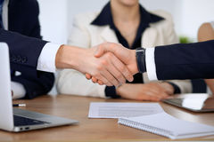 Close up of business people shaking hands at meeting or negotiation in the office. Partners are satisfied because stock photo