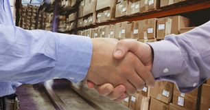 Close-up of business people shaking hands in warehouse. Digital composite of Close-up of business people shaking hands in warehouse Royalty Free Stock Photography