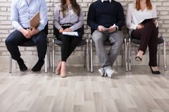 Applicants Waiting For Job Interview. Close-up Of Business People Sitting On Chair Waiting For Job Interview In Office Royalty Free Stock Photos