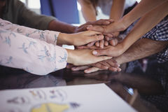 Close up of business people stacking hands. On office desk Stock Image